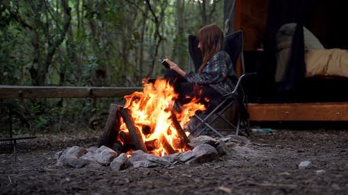 Slow Motion Footage Of A Bonfire With A Woman Reading A Book