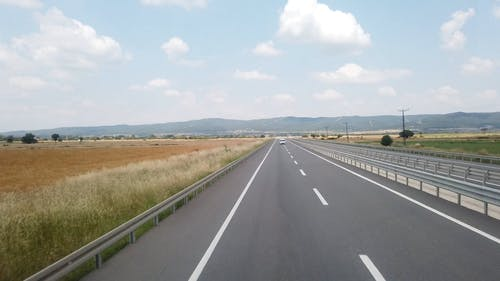 Traveling On A Highway Built Across A Vast Land Of Grass Field