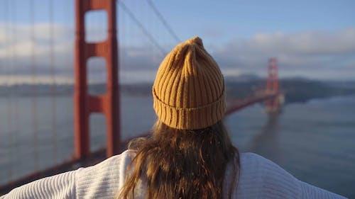 Frau, Die Ein Friedenszeichen Mit Blick Auf Eine Brücke Tut