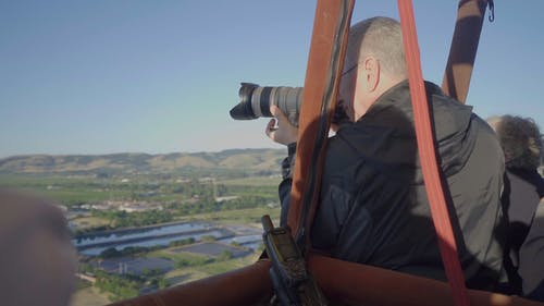 Man Taking Picture Of The Countryside From A Hot Air Balloon