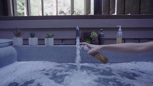 Slow Motion Footage Of Someone Putting Liquid Soap In The Water