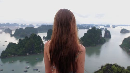 A Woman Standing On A Mountain Top Enjoying The Group Of Islands View