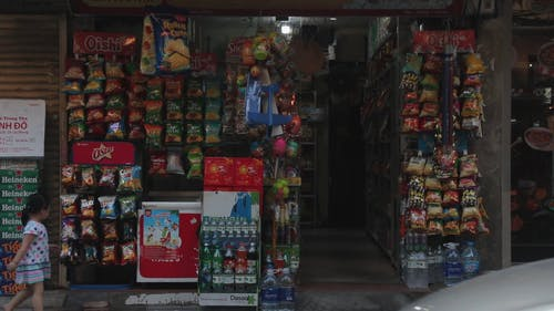 A Convenient Store On The Street Sidewalk Selling Different Goods