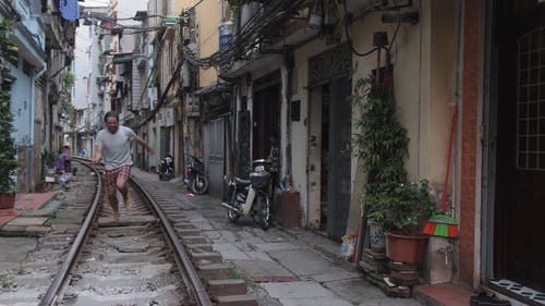 A Man Running Barefooted On The Inside Of A  Rail Track