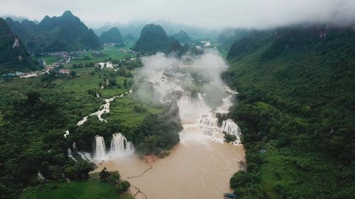 Aerial Footage Of Landscape With Waterfalls On A Foggy Day