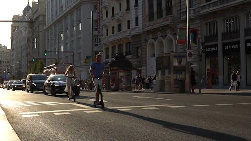 Um Homem E Uma Mulher Usando Carrinhos Motorizados Na Rua