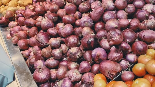 A Hand Getting Red Onions from a Large Pile