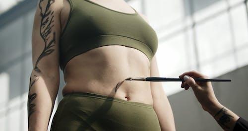 Sich Kitzlig Fühlen, Während Man Eine Körperbemalung Auf Ihrem Bauch Hat