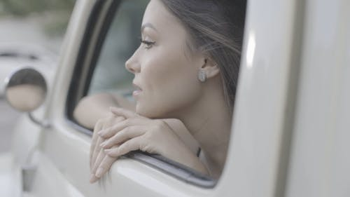 A Woman Looking Outside From The Window Of A Motor Vehicle