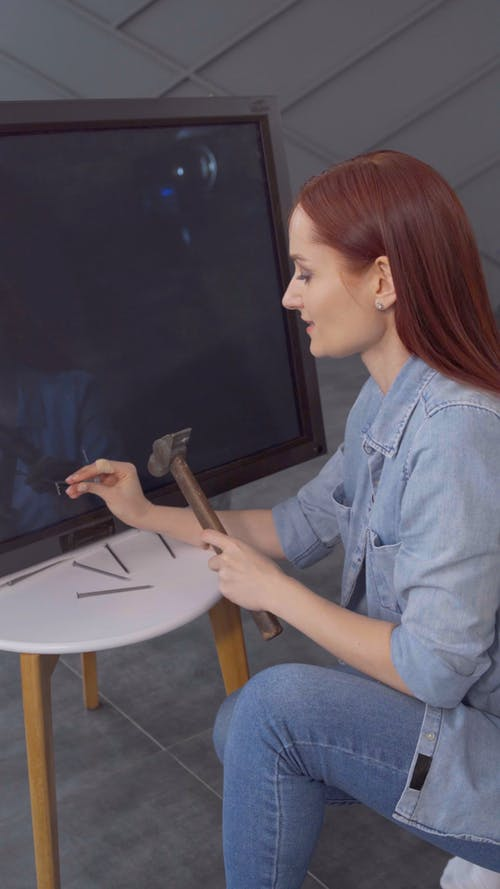 A Woman Totally Breaking A Television Set By Hammering Nail On Is Screen