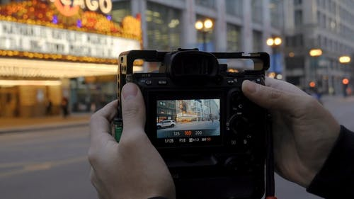 A Photographer Setting Up His Digital Camera To Take A Photo Of Chicago Theater's Frontage