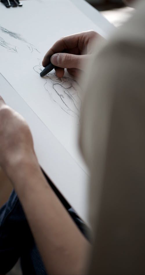 An Artist Sketching A Person Using Charcoal Pencil