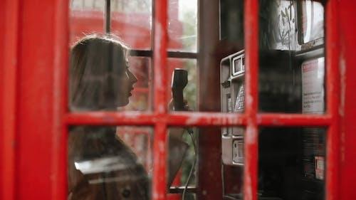 Une Femme à L'aide D'un Téléphone à L'intérieur D'une Cabine Téléphonique