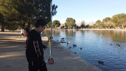 A Kid With His Scooter Standing By The Pond