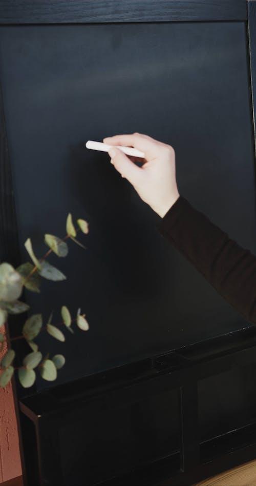 "Writing ""Welcome"" On A Blackboard Using A Chalk"