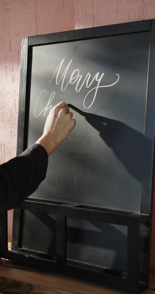 Christmas Greetings Written In Calligraphy On A Blackboard