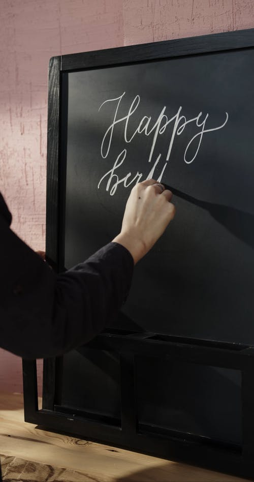 Writing A Birthday Greeting In Calligraphy On A Blackboard Using a Chalk