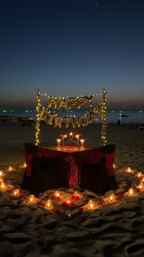 A Birthday Celebration Set-up On The Sand Of A Beach Shore