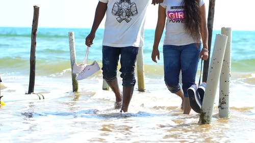 A Couple Walking Barefooted On The Shallow Water Of The Beach Towards The Shore