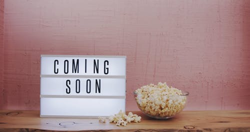 Bowl Of Popcorn Besides A Light Text Box With A Coming Soon Sign