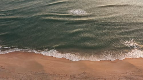 Drone Footage Of A Beach With Small Waves Hitting Its Shore