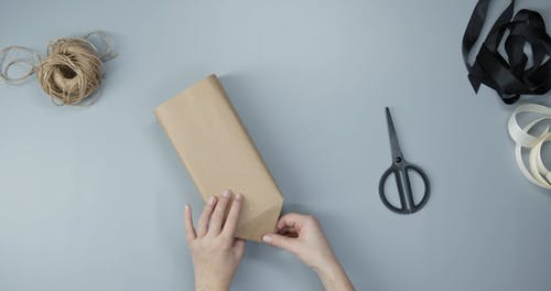 Wrapping A Box With Brown Kraft Paper