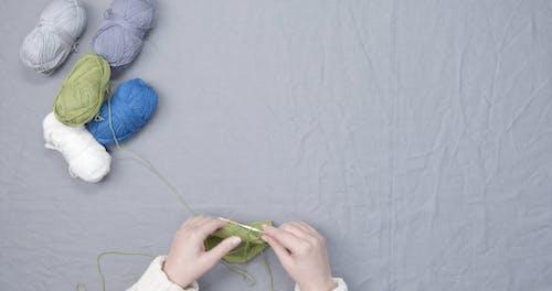 A Person Knitting A Green Thread