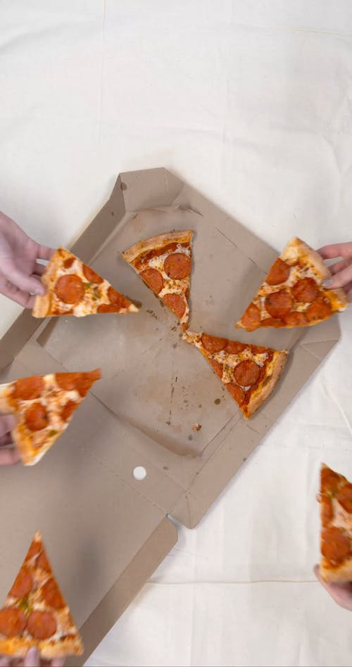 Grabbing A Slice Of Pepperoni Pizza From A Box In A Boomerang Motion