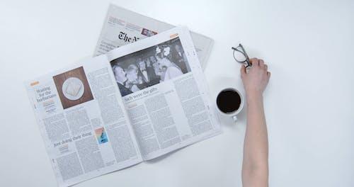 Using An Eyeglass For Reading A Newspaper