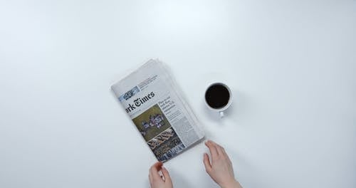 Reading Today's Newspaper Over a Cup Of Coffee