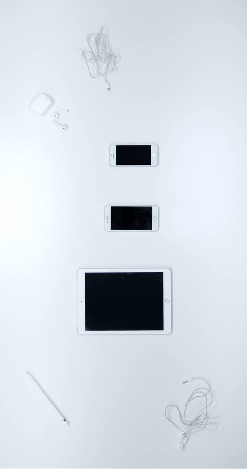 Apple Products Arranged Vertically Over A White Surface