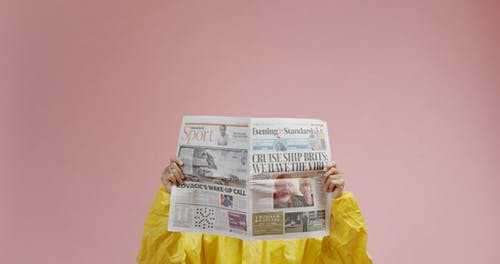 A Man In Protective Suit Is Reading A Newspaper