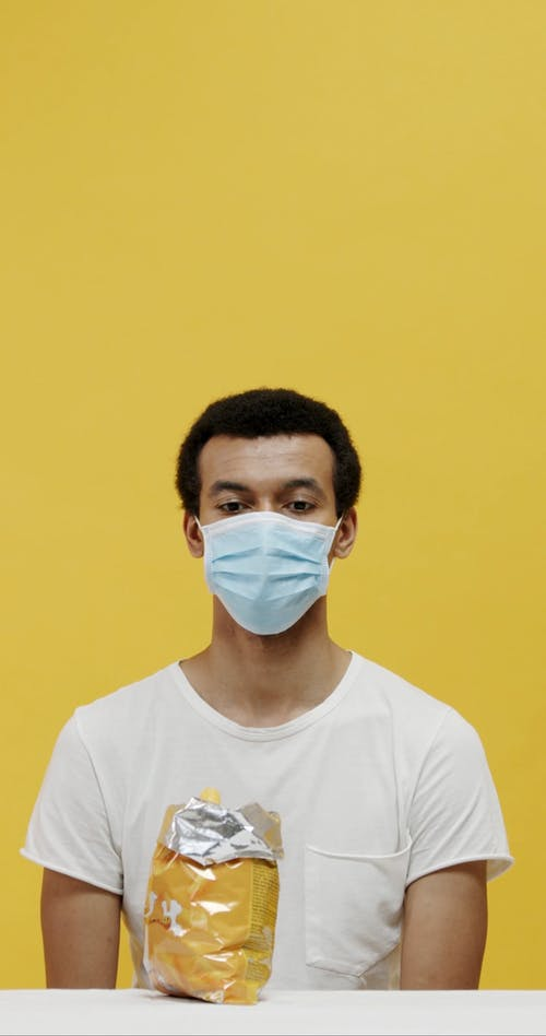 A Man Eating A Sack Behind His Surgical Mask