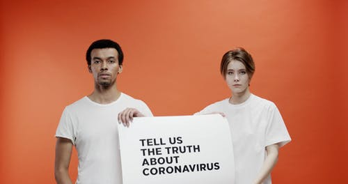 Two People Holding A Slogan Asking About The Truth In Coronavirus