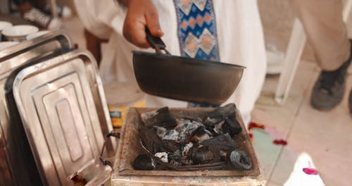 A Woman Roasting Coffee Bean In A Pot Over Burning Charcoals