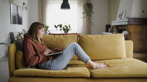 Woman Sitting On A Sofa Using Laptop