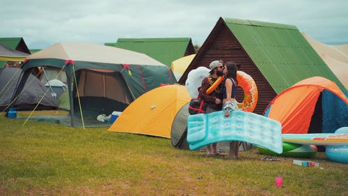 A Couple Kissing Near Camping Tents