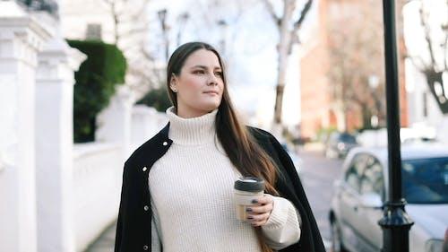 Woman Holding a Cup Walking on Sidewalk