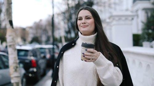 Woman Drinking Coffee While Walking on the Sidewalk