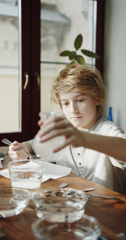 A Boy Mixing A Spoonful Of Vinegar On A Bowl Of Water