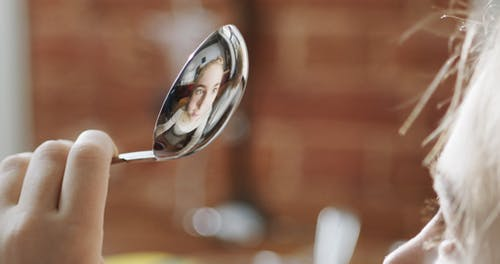 A Girl Using Stainless Spoon As A Mirror