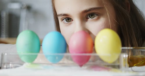 A Girl Waiting For Colored Dye Eggs To Dry