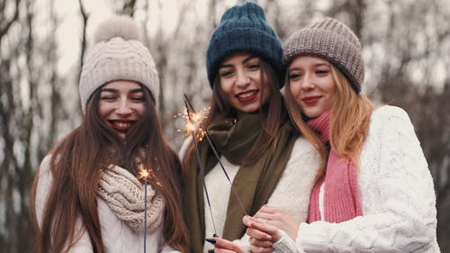 Three Young Women Holding Lighted Stick Sparklers Outdoors