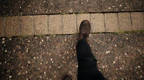 A Person Waking On A Pebblecrete Path