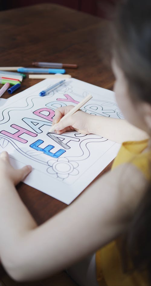 A Girl Coloring A Poster Using Colored Pencils