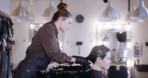 Shampooing A Woman's Hair Over A Basin