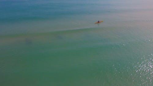A Single Man Paddling A Canoe In The Sea