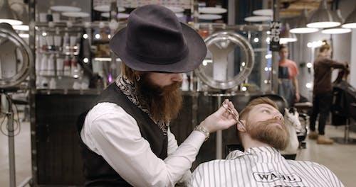 A Barber Trimming A Man's Beard Inside A Salon