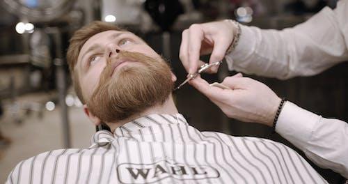 A Barber Using A Scissor In Trimming A Man's Beard