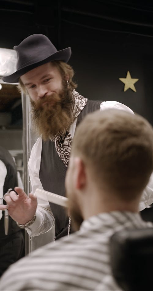 A Barber Grooming A Man's Beard With Scissors